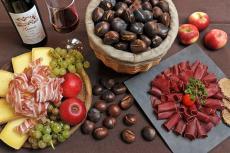 Zu den gerösteten Kastanien werden verschiedene Alpenkäsesorten, Wurstwaren aus Vale, Speck, Äpfel, Trauben und Roggenbrot gereicht.
